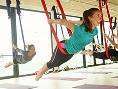 girl smiling in the aerial yoga training