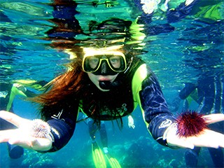 girl diving with sea urchins in both hands