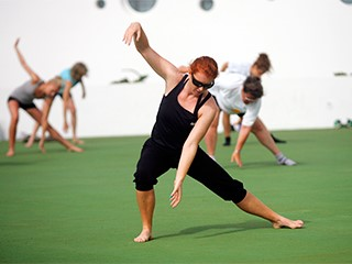 redhaired intructor imparting the femenine fitness class