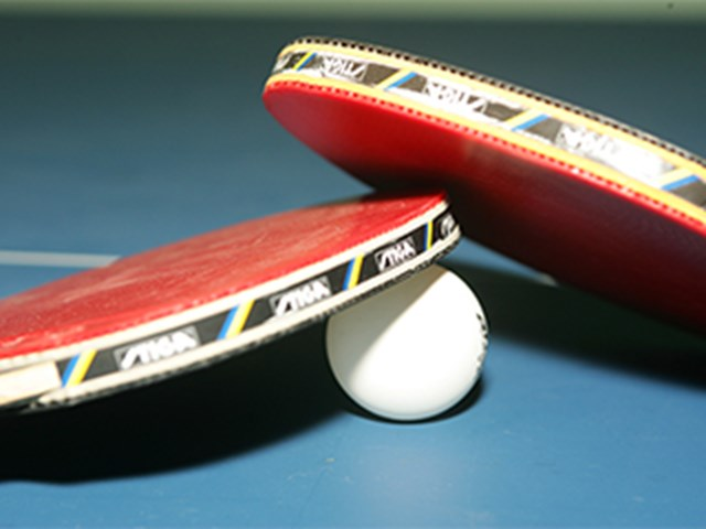 two table tennis rackets and a table tennis ball