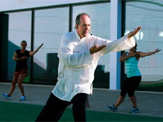 tai chi instructor surrouded by a class